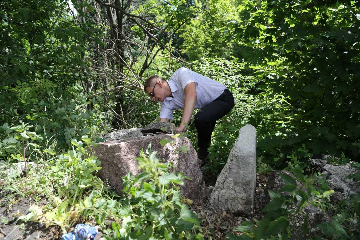 Семен Кропачев пытается под тяжелыми глыбами гранита найти табличку от памятника или фрагмент фигуры бойца, но камни слишком тяжелые