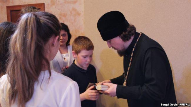 Клирик Симбирской епархии Московского Патриархата протоиерей Андрей Коршунов раздает школьникам иконы.